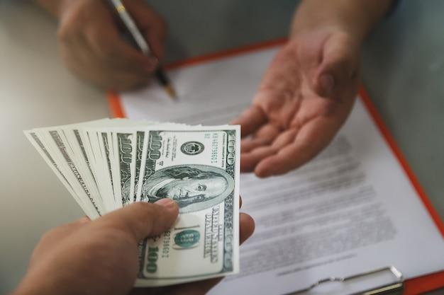 100ドル紙幣のバッチを提供する男。