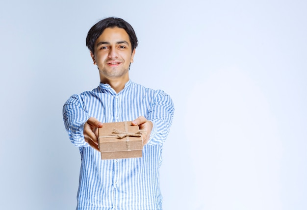 Man offering a cardboard gift box. high quality photo