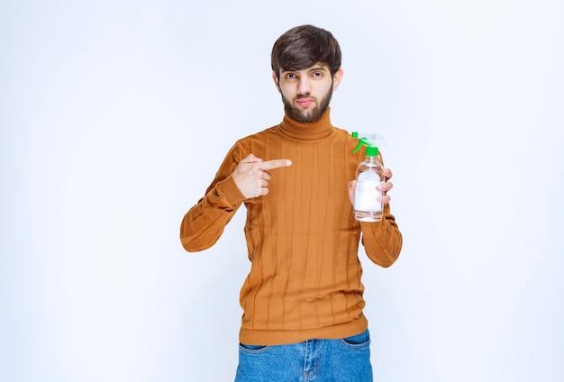 Uomo che offre un prodotto chimico per la pulizia degli interni.