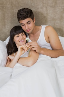 Man offering a flower to woman in bedroom