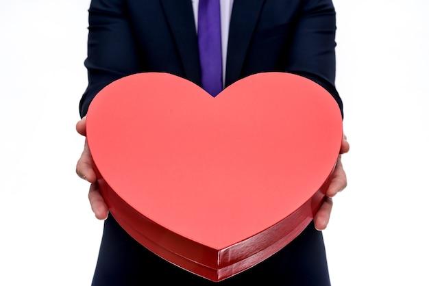 Мужчина предлагает золотое кольцо и большое красное сердце