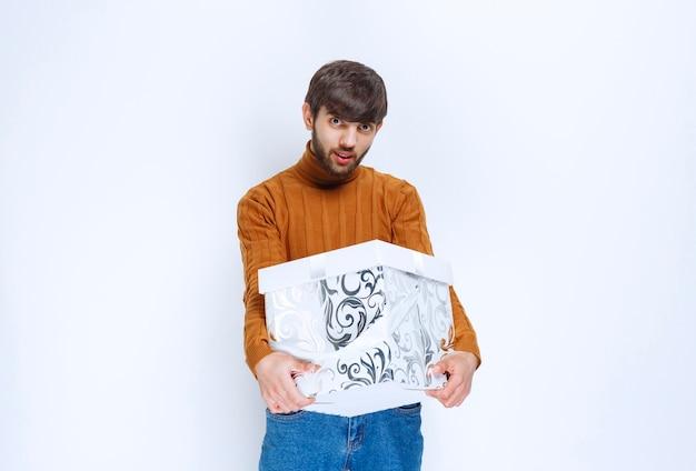 파란색 패턴이있는 흰색 선물 상자를 제공하거나받은 남자.