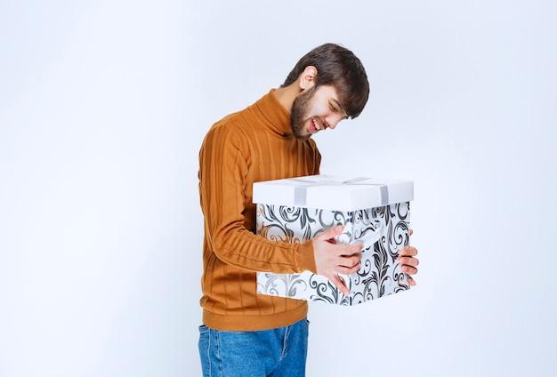 青い模様の白いギフトボックスを提供または受け取った男性。