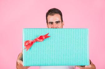 Man offering rectangular gift box standing against pink backdrop