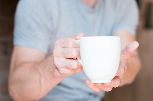 Мужчина предлагает белую чашку энергетического напитка.