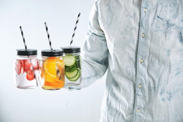 男はイチゴ、オレンジ、キュウリから作られた冷たい新鮮な飲み物が入った瓶を提供しています