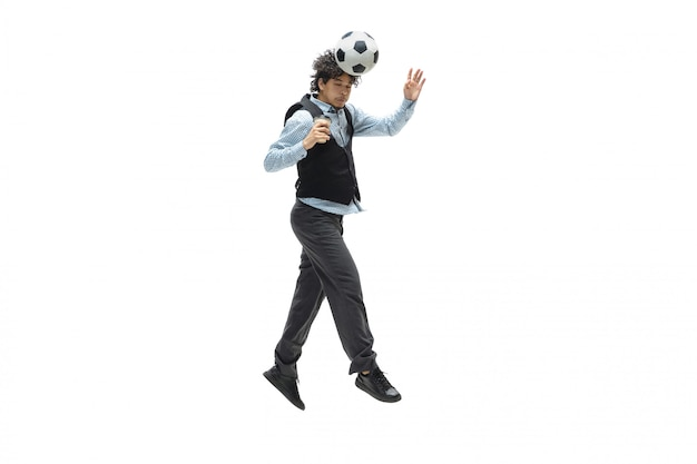 Man in office clothes playing football or soccer with ball on white space. unusual look for businessman in motion, action. sport, healthy lifestyle.