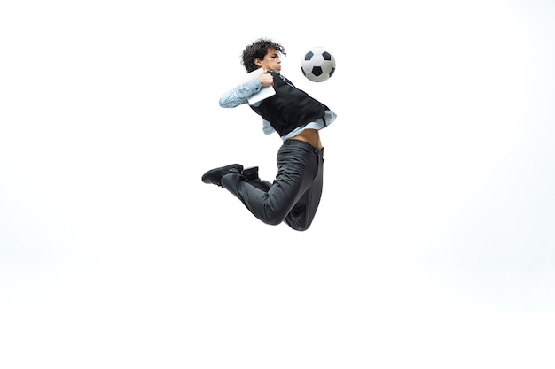 Man in office clothes playing football or soccer with ball on white.