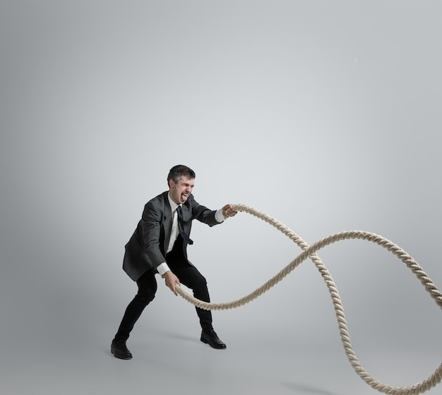 Man in office clothes training with ropes on grey background.