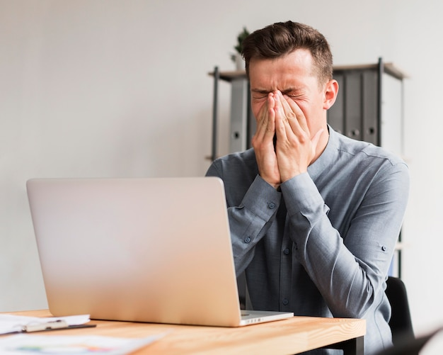 Man in office during pandemic holding his nose