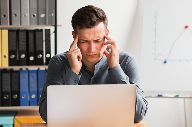 Man in office during pandemic working on laptop and experiencing headache