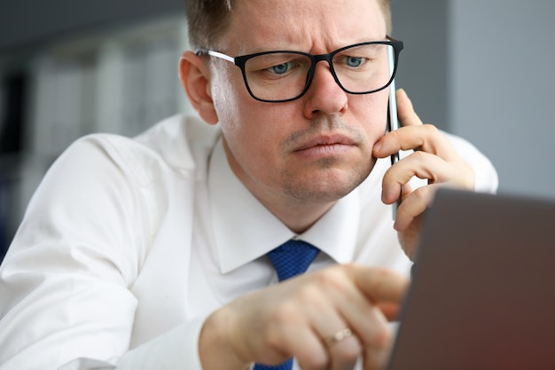 Man in office focused information listens on phone. advantages consulting for doing business. man talks remotely from home during pandemic. manager search and attraction investors