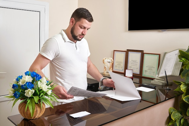Man at office reception desk working with papers for clients