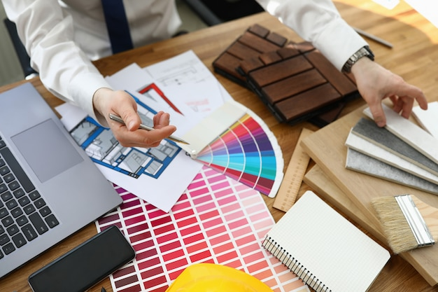 Man in office sits at table with color palette for interior