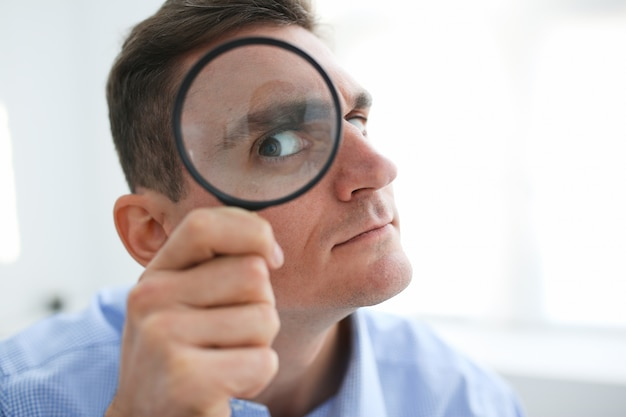 Man in office work holding magnifying glass in hand