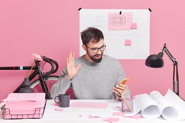 L'impiegato dell'ufficio ha conversazioni in videochiamata con il collega in posa al desktop lavora su pose di progetti di casa nello spazio di coworking