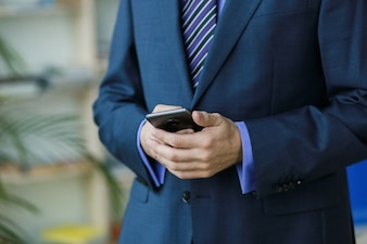 Man office worker in suit with smartphone near window and palm trees