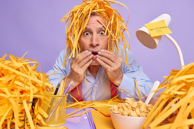 Man office worker stares stupefied has pile of cut paper on head has frightened gaze poses at messy desktop with bowl of cereals folders stickers around