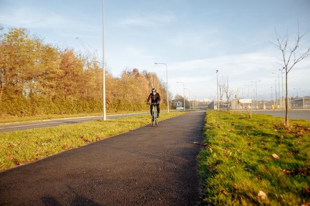 아침 추운 계절에 파란 자전거를 탄 남자가 출근합니다.