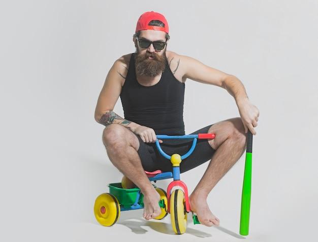 Человек на детском велосипеде велосипедист бородатый сердитый мужчина держит зеленую бейсбольную биту на велосипедной игрушке