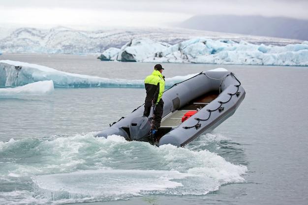 アイスランドの氷河ラグーンを航行する高速モーターボートの男