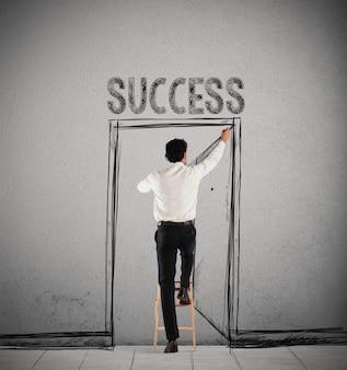 Человек на лестнице с успехом рисует ручкой дверь