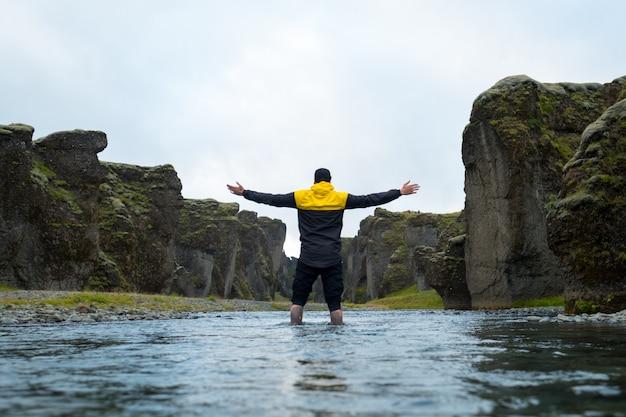山のアイスランドの男。男は、手を空に向けた。自由と自然との一体感。太陽が沈む。景色を楽しむ屋外の観光客。