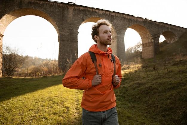 Человек в поездке позирует перед акведуком