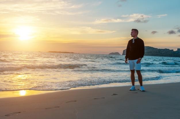 日没時に熱帯のビーチで男