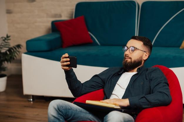 노트북에서 퇴근 후 휴대 전화에서 영화를보고 안락의 자에 남자.