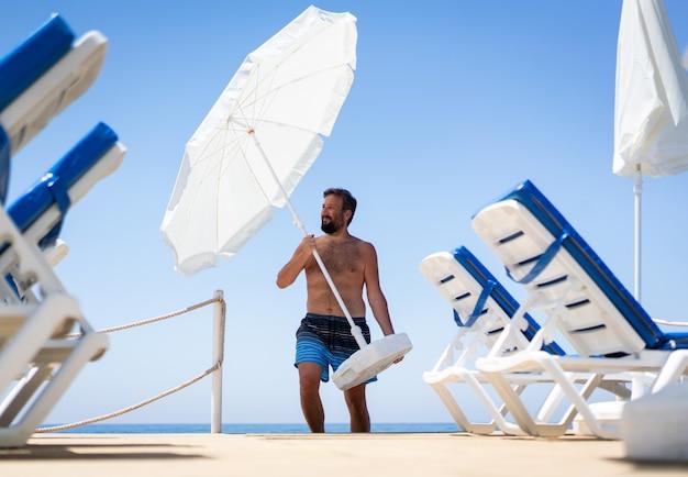 ビーチの桟橋の移動パラソルの男