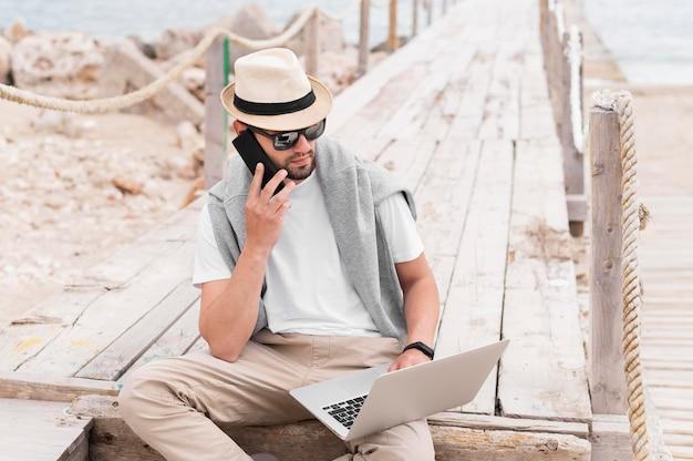 Человек на пирсе пляжа работает на ноутбуке