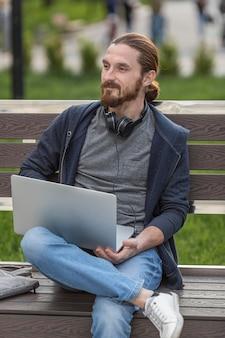 Человек на скамейке на открытом воздухе с ноутбуком