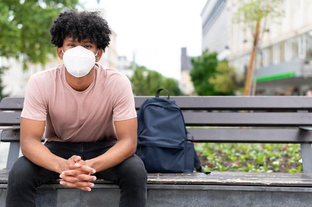マスクを身に着けているベンチの男