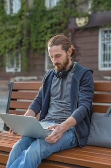 Человек на скамейке работает на ноутбуке