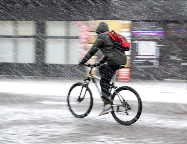 雪の降る冬の日の街で自転車に乗っている男。意図的なモーションブラー。焦点がぼけた画像