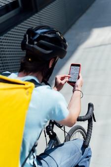 スマートフォンの地図アプリで自転車に乗る男