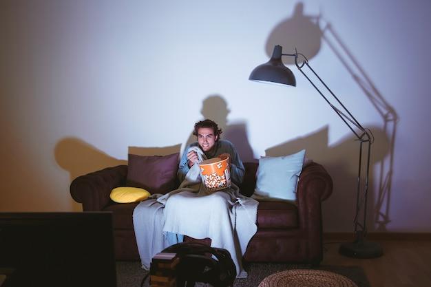 映画の夜を持つソファーの男