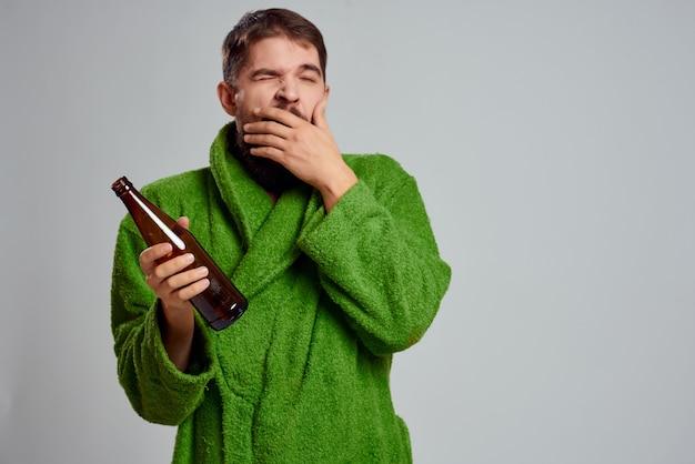 집에서 휴식을 취하면서 맥주를 손에 들고 녹색 가운을 입은 남자