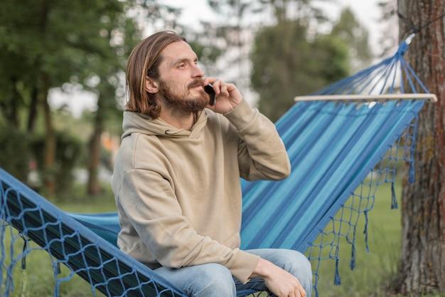 Человек в гамаке на природе, говорить на смартфоне