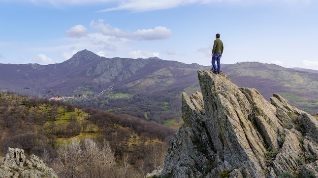 등을 꿇은 남자는 바위가 많은 정상으로 올라가 녹색 산 풍경의 전망을 고민했습니다.