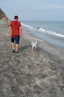 Человек на спине выгуливает собаку утром на пляже