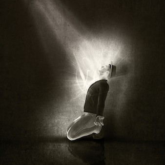 Изображение человека на коленях поклоняясь луч света в интерьере гранж