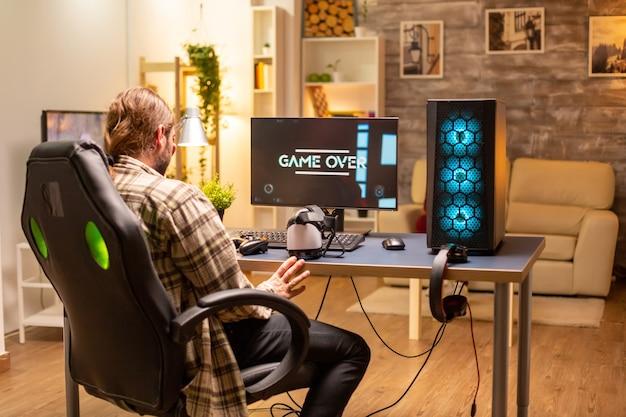 늦은 밤에 거실에서 강력한 pc 컴퓨터를 사용하는 남자가 게임에서 지고 있습니다.