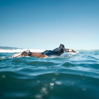 Человек на его доске для серфинга плавание