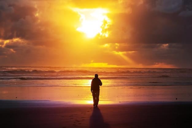日没時のオーシャンビーチの男。休暇の概念の背景。