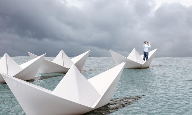 Человек на бумажной лодке с биноклем плывет по морю.