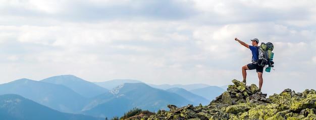 山の頂上の男。感情的なシーン。山の上に上げられた手でバックパックに立って、マウンテンビューを楽しんでいる若い男。山の頂上にハイカー。スポーツとアクティブライフのコンセプト。