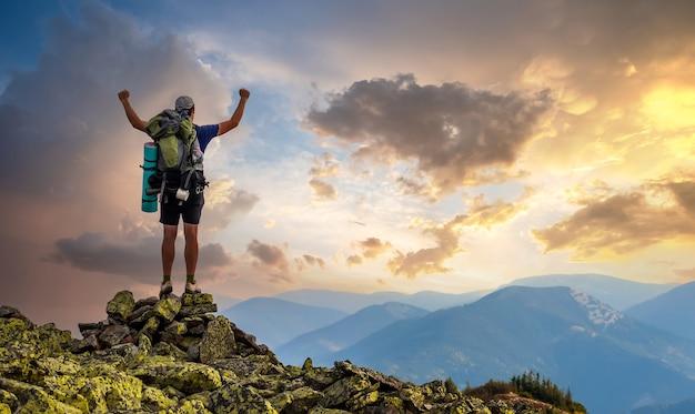 山の頂上にいる男。感情的なシーン。バックパックを持つ若い男