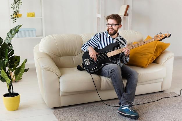 Мужчина на диване у себя дома играет на электрогитаре